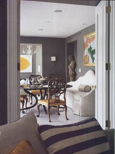 """In this eclectic living room, warm-tone charcoal provides the backdrop for different colors, patterns and lines. It gives the room a nice weight and feels a bit more formal than white would. """"Art jumps off gray walls,"""" Hale says. by BROWN DAVIS INTERIORS, INC."""