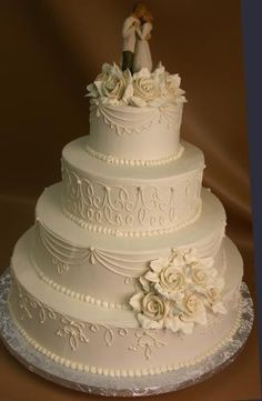 ivory buttercream frosting with white scroll on all layers. Large ivory buttercream roses with white leaves. Side Bouquet and ring around top.