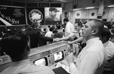 Deke Slayton (in black shirt, left of center) director of flight crew operations, and Chester M. Lee shake hands in Mission Control, while Rocco Petrone watches Apollo 13 commander Jim Lovell on the screen.Image Credit: NASA