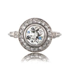 This stunning platinum vintage style engagement ring is set with an old European cut diamond in the center and is surrounded by a row of pave set old mine cut diamonds. The beautiful center diamond is approximately 1.13 carats, H color, SI1 clarity and is very lively.  The old European cut diamond was cut circa 1930.  We can set this ring to any finger size, at no extra cost.  Diamond Age: 1930 Diamond Clarity: SI1 Diamond Color: H Color Diamond Cut: Old European Cut Diamond Certification…