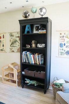 black bookcase in boys room - vintage posters - pale wood floor - globes - armchair - star ceiling - boys room styling