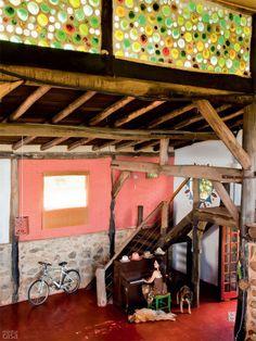 No alto, o encontro das duas águas do telhado tem aberturas (de 1 m de altura) para privilegiar a entrada de luz natural, dispensando o uso de lâmpadas durante o dia em todos os ambientes da casa. Garrafões de vinho, adquiridos de um catador de materiais recicláveis da cidade, foram assentados inteiros com argamassa de cimento e o fundo virado para o interior da construção. Dessa forma, quando o sol bate nas garrafas, o que se vê é um colorido e divertido vitral.