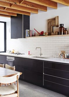 black cabinets, long subway tile, exposed rafters, concrete floor