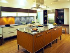 Ample storage and workspace are key in a professional kitchen. This kitchen has both, with a large stainless steel island featuring deep drawers for storage. Design by Troy Adams