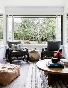 dark bamboo lounge chairs and layered rugs | earthy modern bungalow house tour on coco kelley