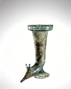Roman glass rhyton, drinking horn, 75-125 A.D. Used for drinking wine, this unusually shaped vessel was designed to terminate in the head of an animal, perhaps a snail, 21 cm high. Corning museum of glass