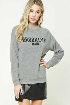 """A heathered knit sweatshirt featuring a """"Brooklyn NY"""" graphic, a round neckline, long raglan sleeves, a fleece lining, and a ribbed trim."""