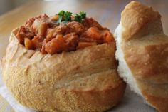 "Bunny Chow. It's got nothing to do with rabbits.  Its a simple serving of curry - any curry - served in a hollowed out loaf of bread.  This dish has its roots in the Indian community of KwaZuluNatal. Eaten with the fingers using the ""lid"" of the loaf to pick out pieces and soak up sauce, it is the ultimate convenience food that is honest and wholesome."