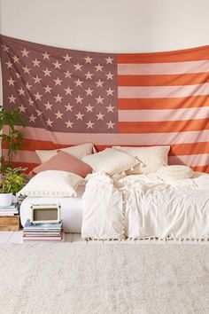 Bed on floor with flag tapestry
