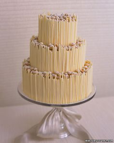 White Chocolate Tower Cake    Tightly-curled tempered-white-chocolate cigarettes create a fortress of three cake layers, which are topped with golden raspberries. A sifting of powdered sugar keeps the raspberries in the color theme.