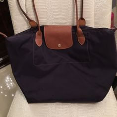 Longchamp plum large le pliage tote Dark purple color, in great shape, minor wear from use, tiny puncture as seen on second picture, leather in great shape, corners of bag were restitched, barely noticeable. Longchamp Bags Totes