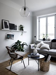 Scandinavian inspired white living room with a round pendant light, a grey couch, a white shelf and a black coffee table.