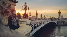 Tourist on Pont de la Concorde in Paris at dusk.