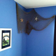Boy's Nautical Themed Bedroom Pic 1- Used fishing net and starfish purchased at Michaels to bring some interest to the empty corner over the bed.