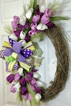 Tulip Wreath on Grapevine. Purple, Lavender and white tulips on an oval grapevine with 3 ribbon Fabric Bow.