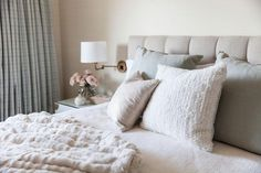 Caitlin Moran - White and beige bedroom features a beige tufted headboard on queen bed dressed in white and beige linen bedding as well as a faux fur throw blanket next to a glass-top nightstand placed under a swing-arm sconce.
