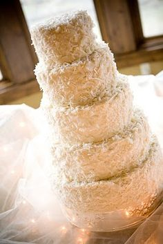 For romantic white texture, and a nod to the tropical menu, the wedding cake would be frosted and sprinkled with coconut flakes