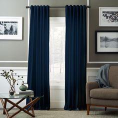Acentúa más tu cuarto con cortinas azules que van desde el techo hasta el piso.