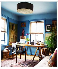 Wonderful John Robshaw office with blue walls and woodwork, drum pendant, wood table.