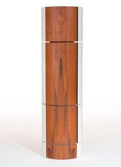 Barschrank aus Tineo. Möbelobjekt in Säulenform mit vier unabhängig voneinander drehbaren Teilen. Material: Tineoholz (Furnier), Biegesperrholz, Floatglas, Edelstahl (Mechaniken), Kork (Flaschenablagen, Glashalterungen). Der Korpus ist mit Buntlack...
