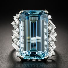 An absolutely  gorgeous, richly saturated, and sleekly proportioned Caribbean blue,emerald-cut aquamarine - weighing 17.50 carats, glistens and glows between diagonal rows of slender straight baguette and round brilliant-cut diamonds in this just shy of 1 inch long and lustrous cocktail ring, expertly hand-fabricated in platinum during the mid-20th century. A refreshing swimming pool for your finger! Currently ring size 6 1/2.