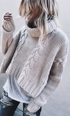 Cable knit sweater over white tee with blue jeans.
