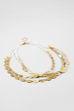 "The Tia Scalloped Gold Necklace is perfect for dressing up any outfit!  This necklaces features three strands of various sized golden scallops that create a sweet but unique look. Pair this with golden accessories & a flowy dress for a complete look!<br /> <br /> - 20.5"" length<br /> - 3.5"" extension<br /> - Lead & nickel free<br /> - Imported"
