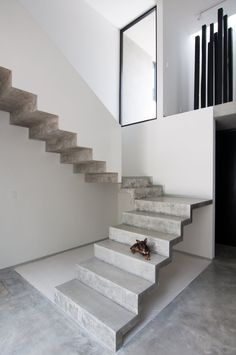 U-shaped concrete cantilevered staircase. From the project Casa Garcias in Cancún designed by Warm Architects