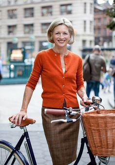 orange + plaid.  Cyclist in the city. Love the outfit; love the bike; love the confident air about this woman.