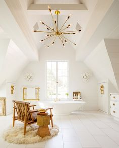 White and brass bathroom featuring a modern chandelier, free standing bathtub, fur rug, and wooden chair.