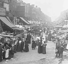 Chapel Market, Islington, London, The street is lined with market stalls and shops, and is bustling with shoppers. A policeman keeps an eye on things in the bottom right corner. Victorian London, Vintage London, Old London, East End London, Victorian Life, Victorian Street, London City, London Pictures, London Photos