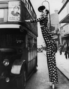 Stilt walking clown Smiler waves his hat at passengers on the top deck of a London bus circa 1940 He is performing with Billy Smart's New World...
