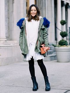Aimee Song wears a fur-trimmed parka with a white dress, black tights and black ankle boots.