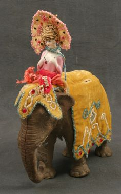 A beautifully dressed girl rides an Elastolin elephant.