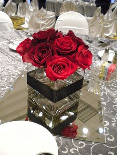 Red rose centerpieces in cube vases with black satin ribbon around vase. Scattered red rose petals on table (no mirror).