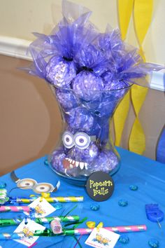 "Popcorn Balls-We used the Rice Krispies recipe, but used popcorn instead...wrapped in purple cellophane and closed up with a twisty tie. Utilized a big vase to display and stuck on the ""bad"" minion goggles and mouth with double sided tape.  And, voila!! Despicable Me Party Favors :) Minions"