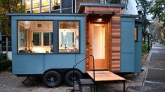 The Verve Lux: a 16 ft tiny home with a living room, kitchen, bathroom and a fold-down deck. Designed and built by Tru Form Tiny Homes!