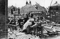 In Liverpool, 68-year-old Sarah Manson sits outside her bombed home with her grandchildren after a German bombing raid