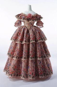 This dress is considered part of the Crinoline era because it has very deep flounces and tiers. It is off the shoulder and is covered in flowers. The crinoline period had a lot of spanish influence and that is where the flounces and the flowers originated from.
