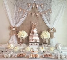 Burlap and lace baby shower sweet bar with diaper cakes and floral arrangements.