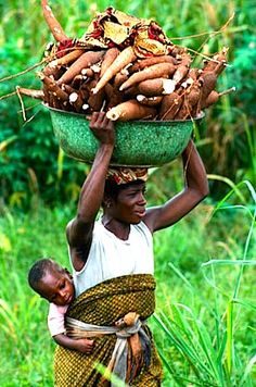 Africa | Woman carrying a child and cassava on her head