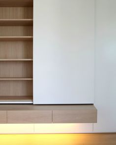 Custom made wall element by German company Holzrausch. The white panel slides to hide a tv behind it.