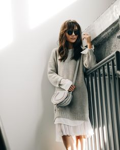 Diana Z Wang wears an oversized knit pullover with a sheer white skirt and a cute mini bag. Outfit: Brochu Walker.