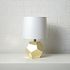 Shop Geometric Gold Lamp.  If you're having a rocky time decorating your home, this table lamp will make things go a bit more smoothly.  It sports a gold base with a unique geometric design that will complement any room in the house.