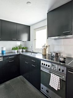 Tummanharmaat, melkein mustat keittiönkaapit on teetetty puusepällä. Tasot ovat mustaa mattapintaiseksi käsiteltyä Nero Assoluto -graniittia. Uunin vetimessä Marimekon Kullervo-keittiöpyyhe.   Vanhan kaupungin helmi   Koti ja keittiö   Jutta Ylä-Mononen   Kuva Kirsi-Marja Savola