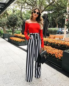 Casual chic off the shoulder red top with black and white striped flared pants.