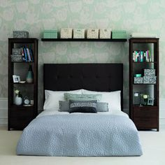 Bedroom with pale green patterned wallpaper and dark wood furniture