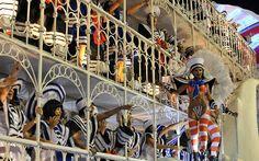 Members of Uniao da Ilhia samba school perform atop a float