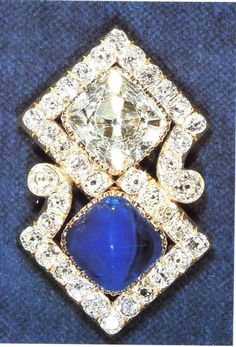 Queen Mary's Russian Brooch.  It was originally given by Empress Marie Feodorovna of Russia to Princess May of Teck (later Queen Mary) as a wedding present in 1893. The brooch has a large square-cut diamond and square cabochon sapphire set in a scroll frame of round diamonds. The Empress later asked her husband, Alexander III, to add a matching sapphire and diamond bracelet to the gift. The Queen inherited the brooch in 1953, when Queen Mary passed away.