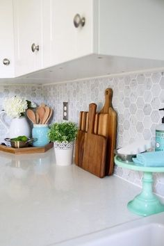 Kitchen accessories, cutting boards, Carra marble backsplash. Beautiful white IKEA SEKTION GRIMSLOV kitchen with aqua and green accents, a gorgeous marble hexagon backsplash, and quartz countertops. | JustAGirlAndHerBlog.com #homekitchen